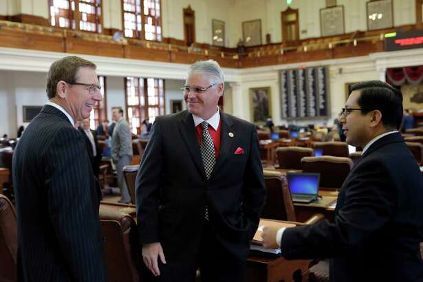 Rep. Dan Huberty, R-Houston, center, talks with Rep. Byron Cook, R-Corsicana, left, and Rep. Diego Bernal, D-San Antonio, right, on the house floor Wednesday, April 19, 2017, in Austin, Texas. Huberty, Chair of the House Public Education Committee, is the sponsor of House Bill 21 which would put money into the school system. (AP Photo/Eric Gay)