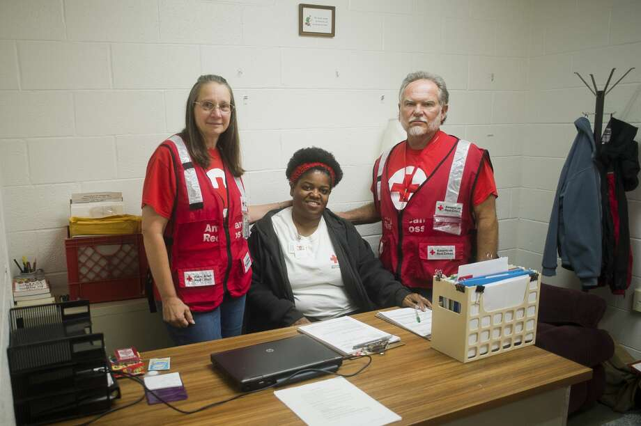From left to right, Red Cross volunteers Cynthia Woiderski of Midland, Sharron Hall of Flint and Larry Woiderski of Midland pose for a portrait inside a Red Cross shelter at the West Midland Family Center at 4011 W. Isabella Road on Monday, June 26, 2017. Photo: (Katy Kildee/kkildee@mdn.net)