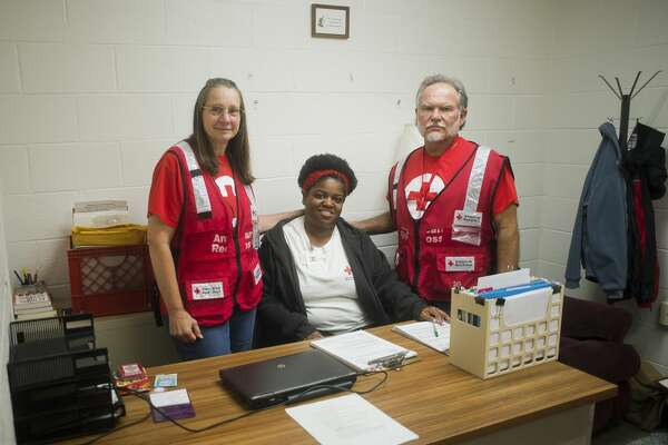 From left to right, Red Cross volunteers Cynthia Woiderski of Midland, Sharron Hall of Flint and Larry Woiderski of Midland pose for a portrait inside a Red Cross shelter at the West Midland Family Center at 4011 W. Isabella Road on Monday, June 26, 2017.