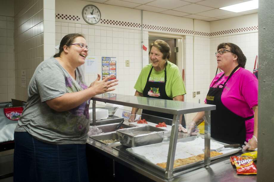 Merrill resident Carmen Lang, left, chats with Sharon Venard, center, and Sherry English, right, both of Midland, as Venard and English serve lunch to Lang and her children, who regularly participate in the Meet Up and Eat Up program, on Monday, June 26, 2017 at Floyd Elementary. The school is offering free meals Monday through Friday from 9 a.m. until 10 a.m. and from noon until 1 p.m. for anyone impacted by Midland's recent flooding. Photo: (Katy Kildee/kkildee@mdn.net)