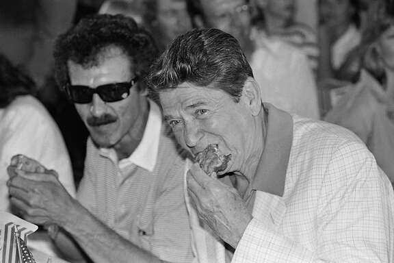 President Ronald Reagan, right, and driver Richard Petty  eat fried chicken July 4, 1984, at Daytona International Speedway.