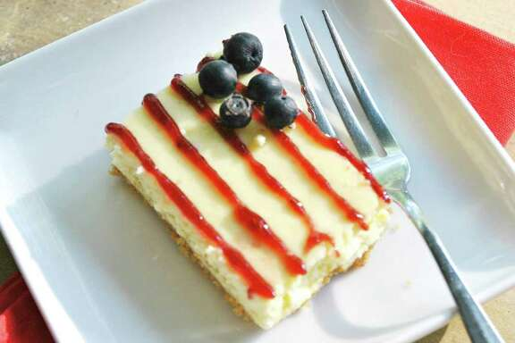 American Flag Cheesecake Bars use raspberry-jam piping for the stripes and blueberries for the stars.