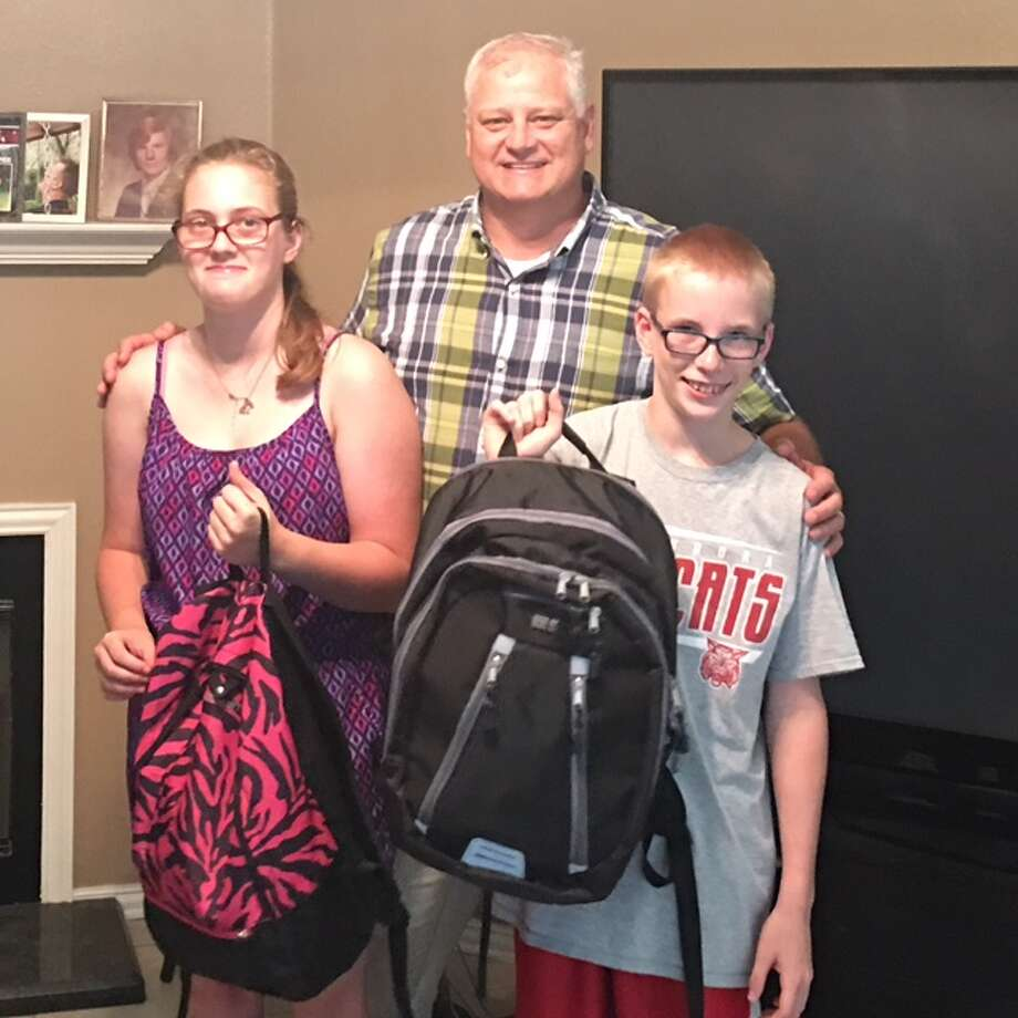 Lion Scott Perry, center, delivers backpacks full of goodies from the Conroe Noon Lions Club, to Amber, left, and Carson Free as they head off for a week long camping session at Texas Lions Camp in Kerrville, Texas. Photo: Submitted Photo
