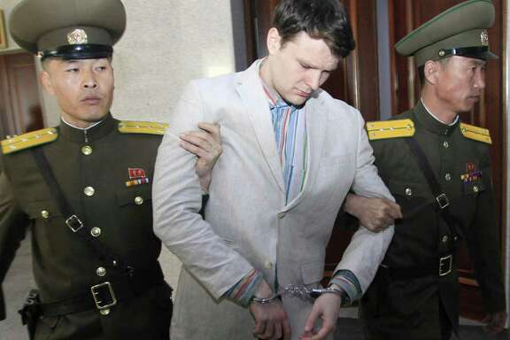 American student Otto Warmbier, center, is escorted at the Supreme Court in Pyongyang, North Korea, Wednesday, March 16, 2016. North Korea's highest court sentenced Warmbier, a 21-year-old University of Virginia undergraduate student, from Wyoming, Ohio, to 15 years in prison with hard labor on Wednesday for subversion. He allegedly attempted to steal a propaganda banner from a restricted area of his hotel at the request of an acquaintance who wanted to hang it in her church. (AP Photo/Jon Chol Jin)