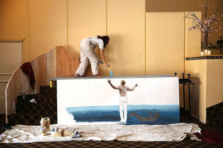 Teacher and artist Alexis Orth works on the baptismal in the church at Old Rey Theater in San Francisco last year. Photo: Liz Hafalia, The Chronicle