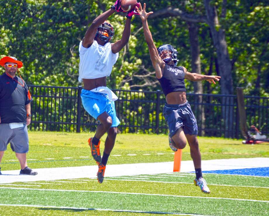 Edwardsville wide receiver Donovan Booker, left, catches a pass over a Washington (Mo.) cornerback Saturday.