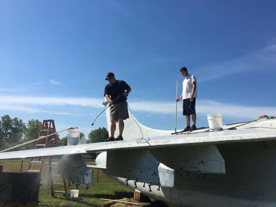 Volunteers with the Flight Deck Veterans Group and the community wash more than 25 years of dirt and debris off the aircraft. Photo: For The Intelligencer