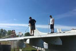 Volunteers with the Flight Deck Veterans Group and the community wash more than 25 years of dirt and debris off the aircraft.