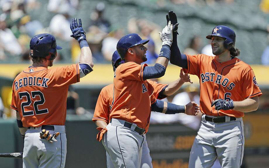 Houston Astros' Jake Marisnick, right, is congratulated by Josh Reddick (22) and Yuli Gurriel, center, after hitting a three-run home run off Oakland Athletics pitcher Jesse Hahn in the first inning of a baseball game Thursday, June 22, 2017, in Oakland, Calif. (AP Photo/Ben Margot) Photo: Ben Margot, Associated Press