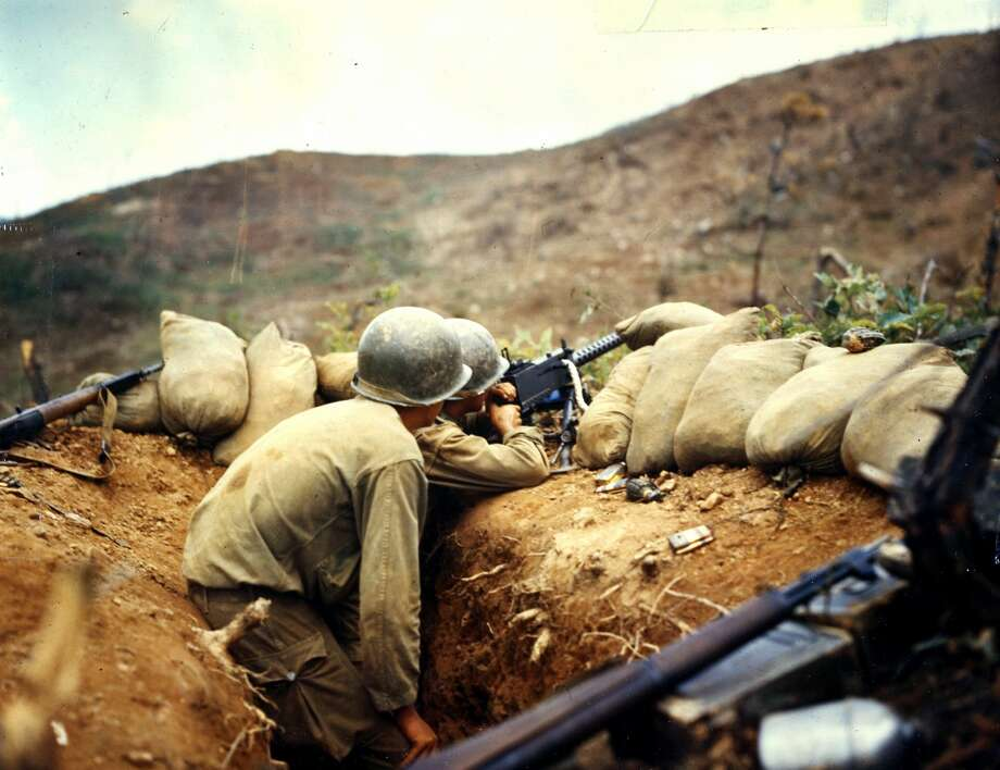Two soldiers train their 30 caliber machine gun on Communist positions on the western front, during the Korean War, July 1952. Photo: PhotoQuest/Getty Images