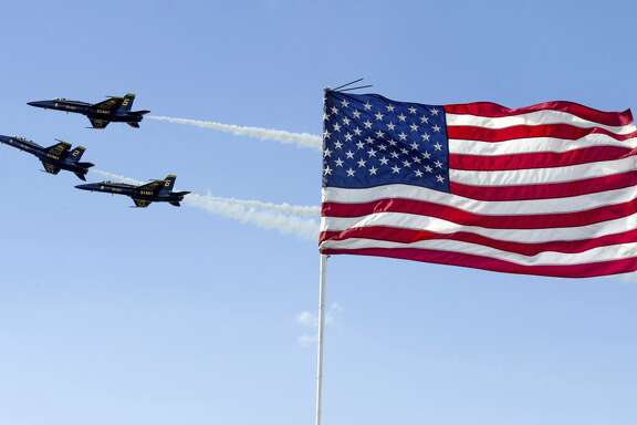 The United States Navy Blue Angels fly past an American flag during the Westmoreland County Airshow on Sunday, June 25, 2017, at Arnold Palmer Regional Airport in Westmoreland County, Pa. (Steph Chambers/Pittsburgh Post-Gazette via AP)