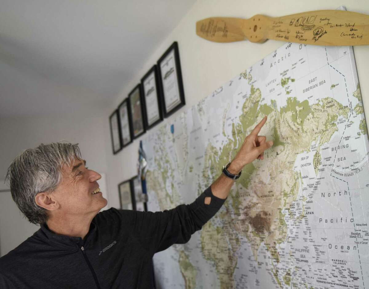 Scientist and explorer Luc Hardy points to places he has traveled on a large map in his home in the Cos Cob section of Greenwich, Conn. Monday, June 26, 2017. Hardy has been captained many climate change-themed scientific excursions and plans to go to Cuba and Russia later this year.
