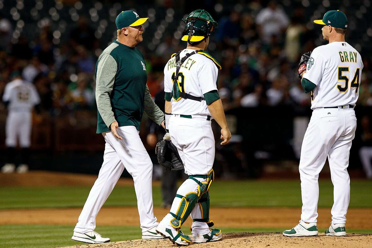 OAKLAND, CA - JUNE 15: Scott Emerson #65 of the Oakland Athletics meets with Sonny Gray #54 and Josh Phegley #19 on the pitchers mound during the sixth inning against the New York Yankees at the Oakland Coliseum on June 15, 2017 in Oakland, California. The Oakland Athletics defeated the New York Yankees 8-7 in 10 innings. (Photo by Jason O. Watson/Getty Images)