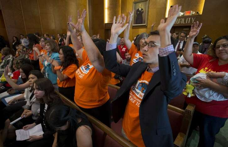 People  raise their hands in support of state Sen. Sylvia Garcia's comments at a  Houston City Council meeting in favor ofthe city joining a lawsuit challenging Senate Bill 4.
