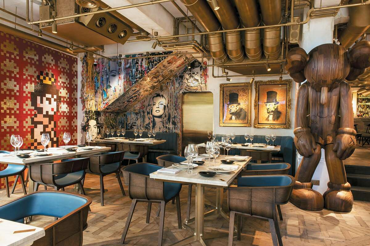 """A discreet gold door? A tuxedoed doorman? Is this """"Twin Peaks?"""" No, this is Bibo, an outlandishly extravagant French restaurant where contemporary fine dining meets, wait for it, street art. From """"Hong Kong Precincts"""" by Penny Watson."""