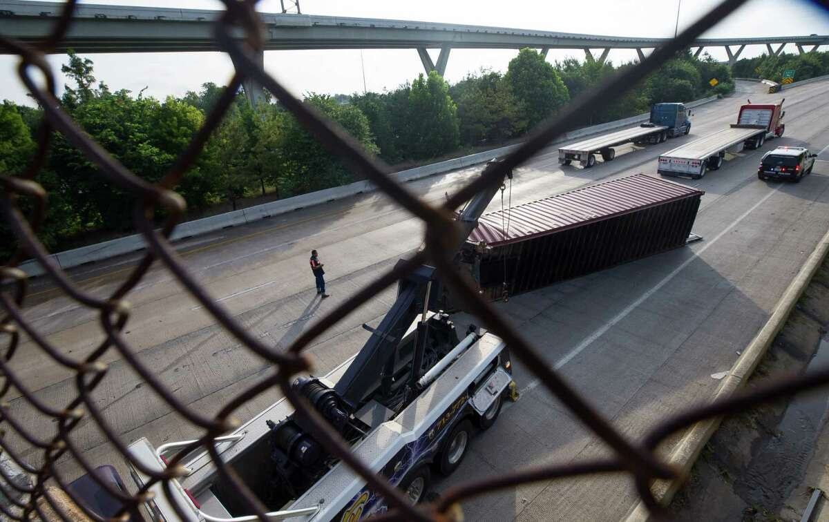 One driver was hospitalized Monday after a tall truck struck the Houston Avenue overpass on Interstate 10 while carrying an intermodal container used in shipping.