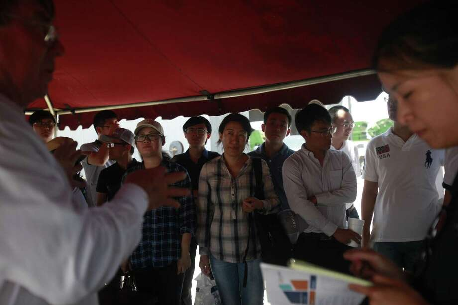 A group of 14 Chinese grain buyers gather at a farm in Sinton to learn about growing grain sorghum. The visitors listened to Charles Ring, the owner of Ring brother farms, as Stella Qian, U.S. Grains Council manager of trade terms, translated. Photo: Srijita Chattopadhyay /San Antonio Express-News / © 2017 San Antonio Express-News