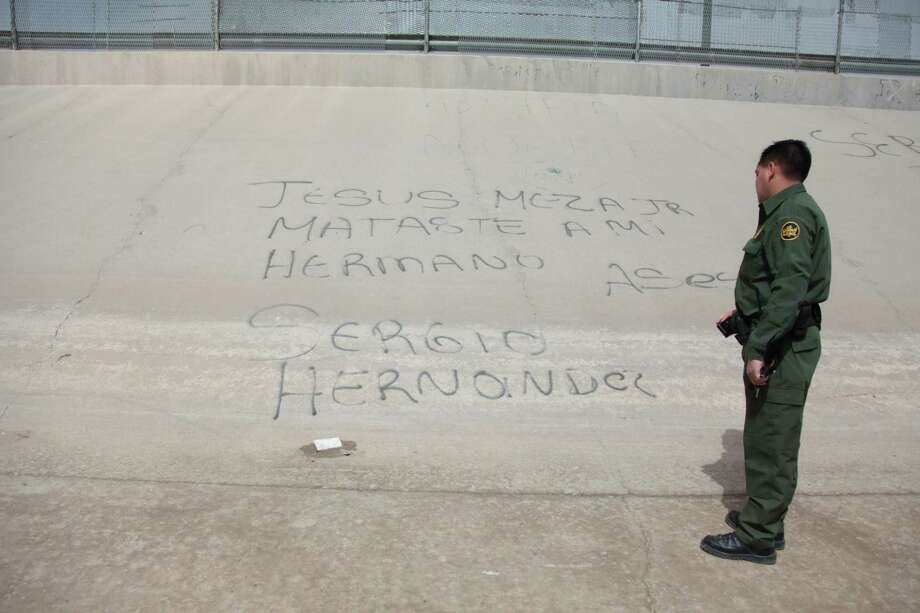 "Border Patrol Agent John Urquidi reads graffiti written by Mexican Nationals along the banks of the Rio Grande on Monday, March 19, 2012, in El Paso. The graffiti translates to ""Jesus Meza Jr. you killed my brother Sergio Hernandez... Murderer."" This refers to Border Patrol Agent Jesus Meza who shot and killed 15-year-old Sergio Adrián Hernández in June 7, 2010. ( Mayra Beltran / Houston Chronicle ) Photo: Mayra Beltran, Staff / Houston Chronicle / © 2012 Houston Chronicle"