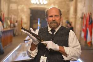 """Alamo Historian and Curator Dr. Bruce Winders displays the """"Firearms of the Texas Frontier, Flintlocks to Cartidge (1836-1876) which will be on display in the Alamo Shrine through April 15, 2015. He is holding a Colt Walker pistol."""