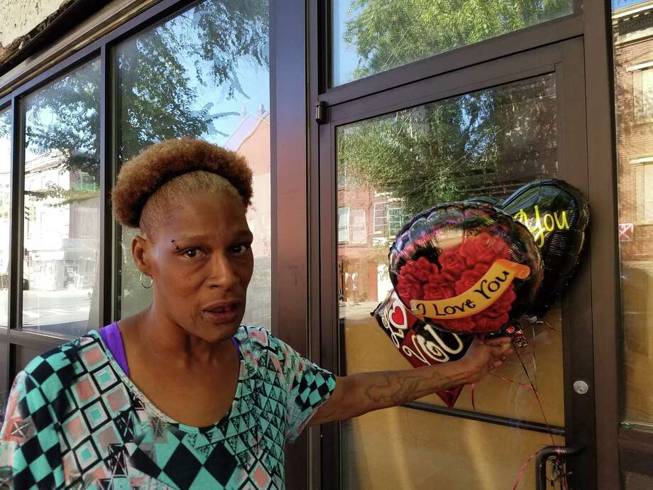 Monick Johnson, a friend of homicide victim Marc Douglas, 47, who died after being stabbed early Sunday morning on Grand Street in Albany, holds balloons purchased to mark the man's passing. (Chris Churchill / Times Union)
