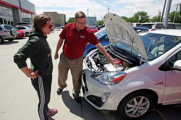 Salesman Doug Lund shows the engine of a Prius C hybrid to Mary Jean Jones in Salt Lake City. Auto sales have declined for five straight months.