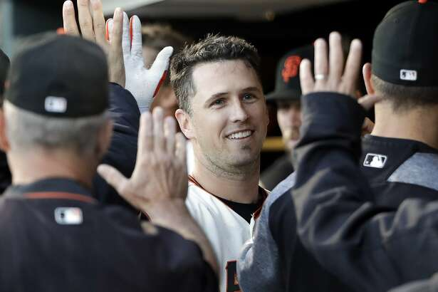 San Francisco Giants' Buster Posey, center, high-fives teammates in the dugout after driving in a run with a sacrifice fly ball during the third inning of a baseball game against the Colorado Rockies Monday, June 26, 2017, in San Francisco. (AP Photo/Marcio Jose Sanchez)