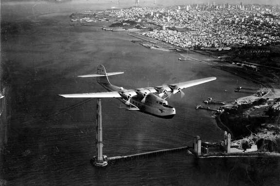 1935: One of the first passenger airplanes flies over the unfinished Golden Gate Bridge in San Francisco. The China Clipper was a pioneer for air travel in the U.S.