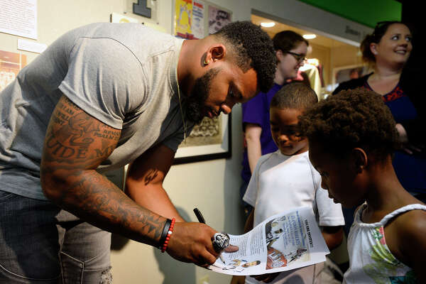 New England Patriots linebacker Elandon Roberts signs an autograph for Jeremy Johnson, 8, and Eriyohn Mickens, 6, during an induction ceremony into the Museum of the Gulf Coast's sports hall of fame on Monday. Photo taken Monday 6/26/17 Ryan Pelham/The Enterprise