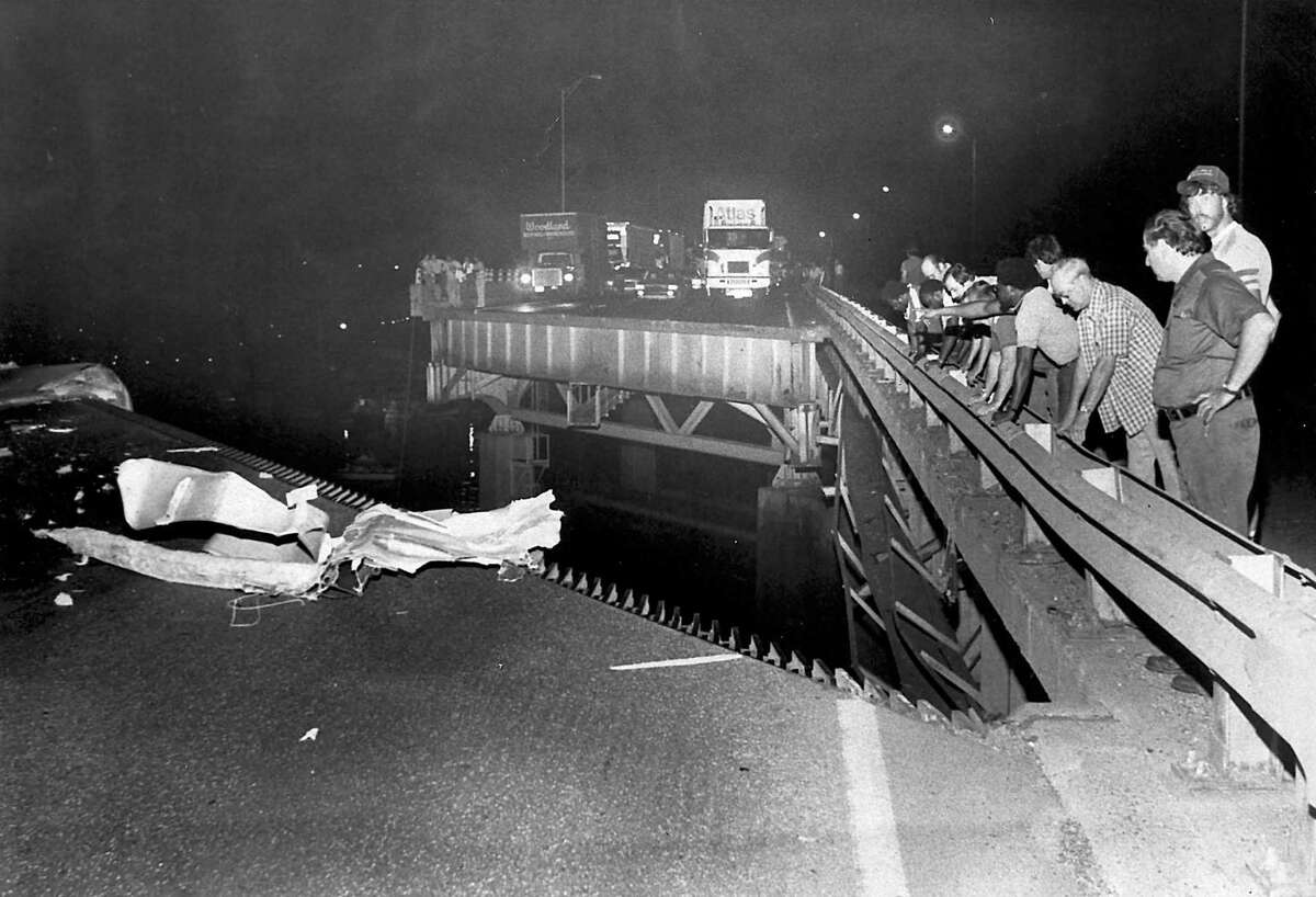 Spectators look at the damage the night of the Mianus River Bridge collapse June 27, 1983.