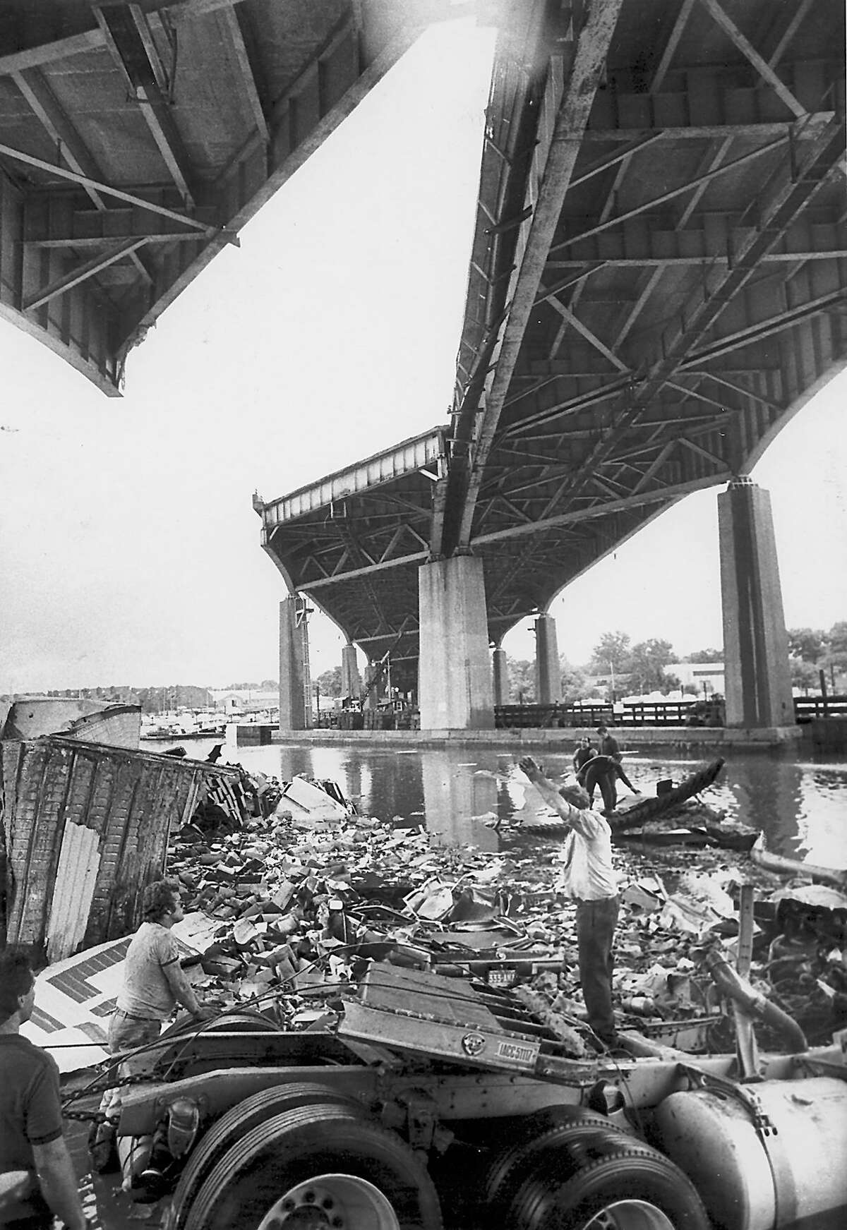 Mianus River Bridge Collapse June 28, 1983 - Tow operators attempt to clear wreckage under I-95. In foreground is part of the tractor trailer truck that fell. Photo/Tom Ondrey b/w