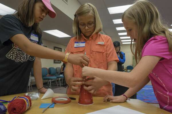 Brylee Russell, Sarah Masonheimer and Alli Watkins work on their design 6/26/17 during the SciGirls STEM Camp at Midland County Library downtown branch. The girls tried to design and build a devise to measure wind speed. Tim Fischer/Reporter-Telegram