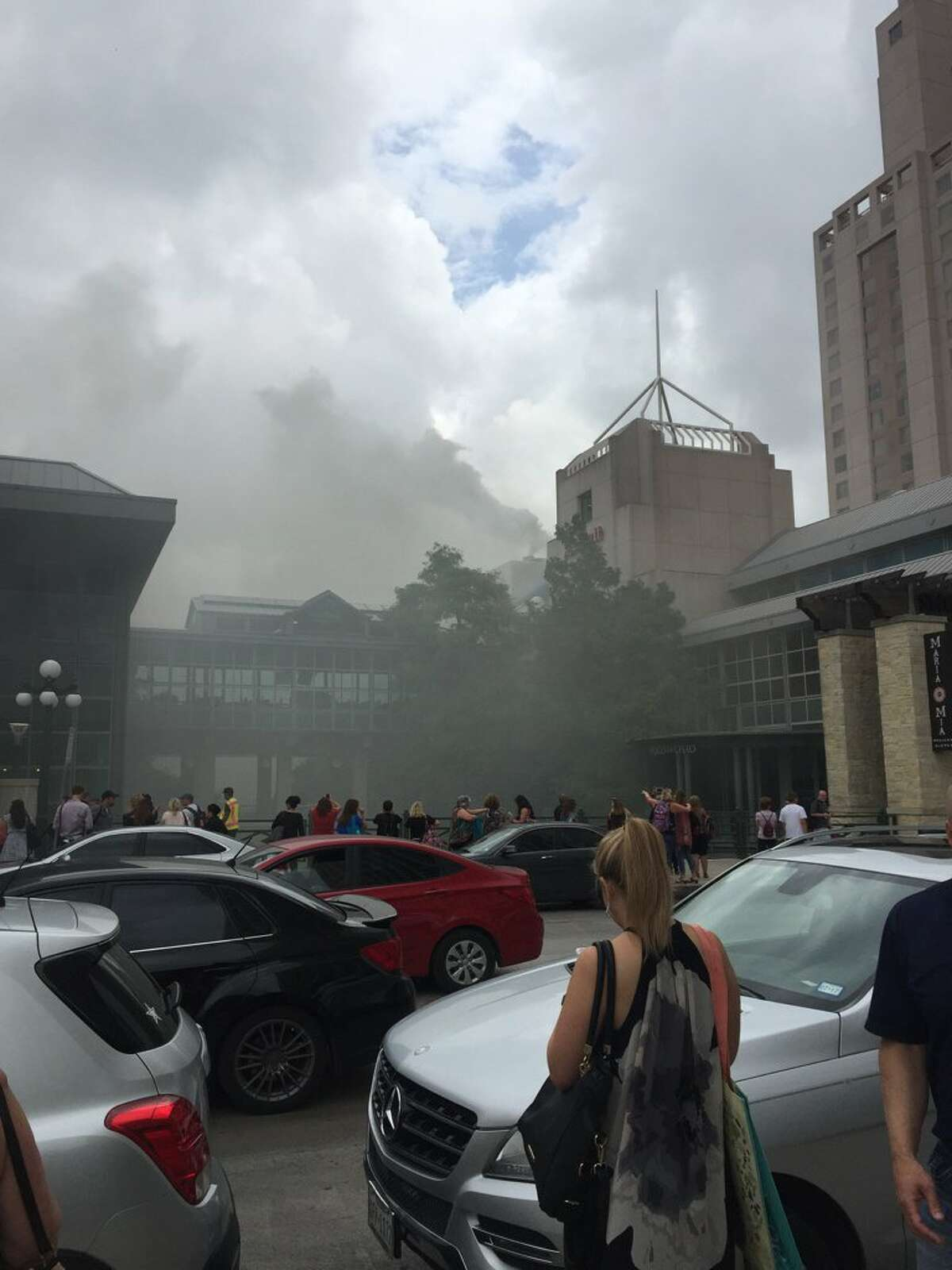 Smoke can be seen pouring from the area around the Shops at Rivercenter downtown as emergency personnel respond to a reported fire in the area.