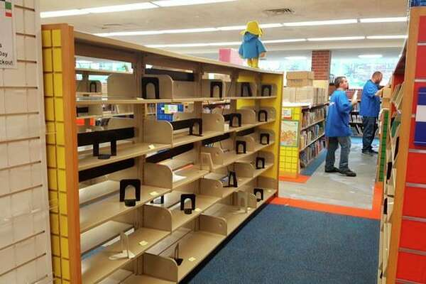 ServPro workers remove books from shelving in the library's lower level on Monday.