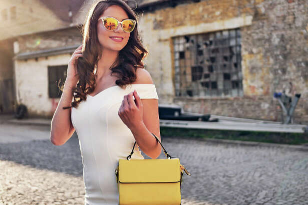 Portrait of beautiful and elegant young woman in haute couture or street style clothing, in rustic part of downtown in big European city.