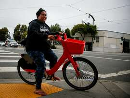 Stella Maloa, Project Bayou Women's House mentor, rides a new electric Social Bike, a bike sharing pilot, outside the Huli Huli Hawaiian Grill  in San Francisco on Sunday, June 25, 2017.