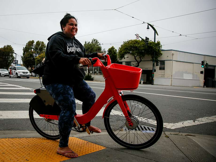 Stella Maloa, Project Bayview Women's Home mentor, rides a new electric Jump bike from Social Bicycles, part of a bike-sharing pilot, outside the Huli Huli Hawaiian Grill in San Francisco. The Bay Area's first e-bike-sharing program put 100 neon-red bicycles on San Francisco streets this week. Photo: Nicole Boliaux, The Chronicle