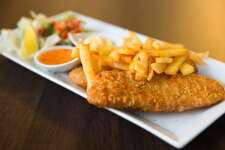 The horizontal image of deep fried fish fillet topped with french fries with sauce on a white plate.
