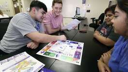 Northwest Vista College students Sergio Gonzalez and Chandler Gull work out their math paths in their student development class with a game developed by instructors to steer students toward math courses appropriate to their degree plans. Also pictured are Yesenia Rodriguez and Thalia Moreno. The college found that taking the wrong math courses are a prime stumbling block to completing degrees.
