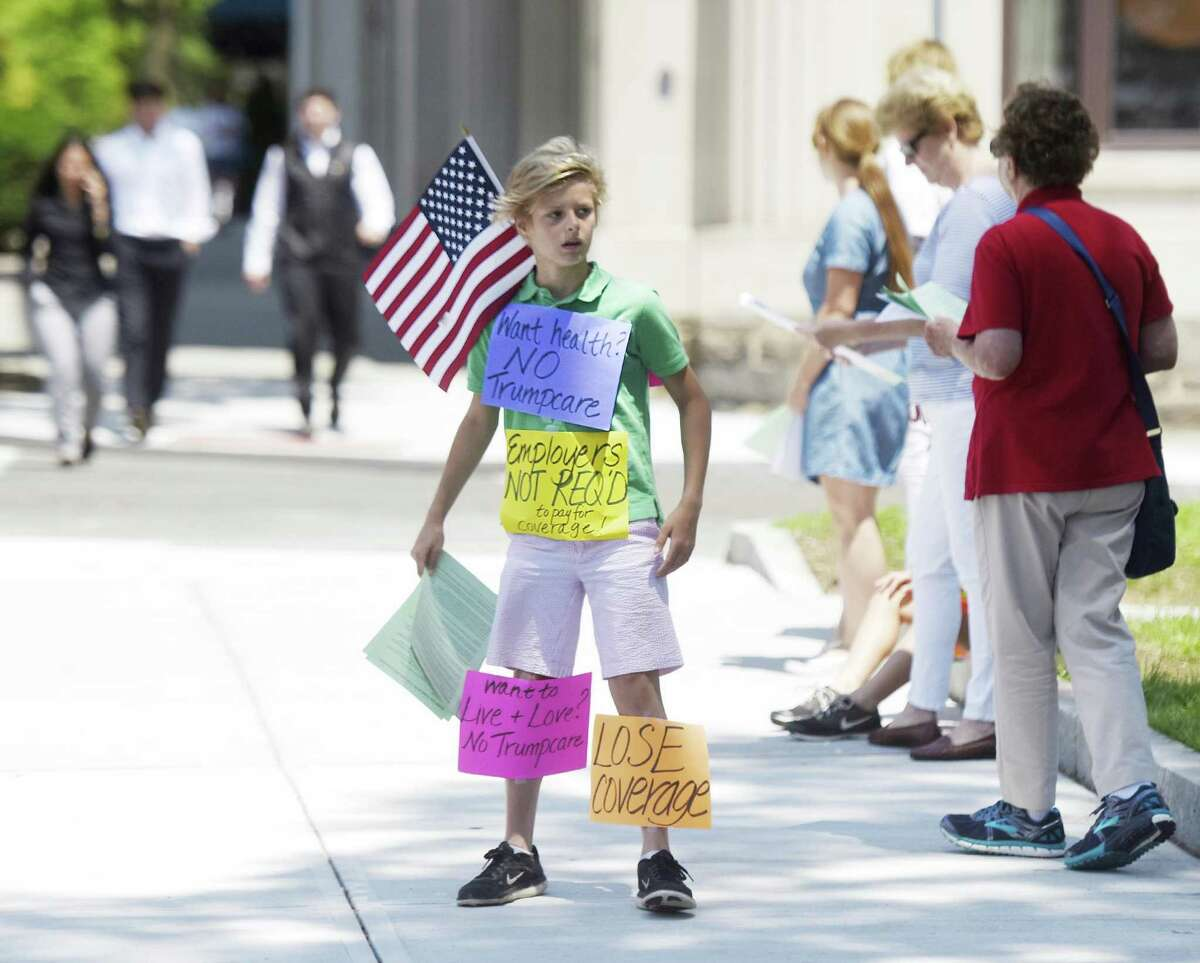 Riverside's Tyler Fahey, 11, shows an array of signs during the anti-Trump group Indivisible Greenwich's protest against the new proposed American Health Care Act outside the Senior Center in downtown Greenwich, Conn. Tuesday, June 27, 2017. The group gave fact sheets about the new proposed healthcare and urged passersby to call their Senators. Facing opposition from both parties, Senate Majority Leader Mitch McConnell announced Tuesday he would delay consideration of the bill until after the Senate's weeklong July 4 recess.