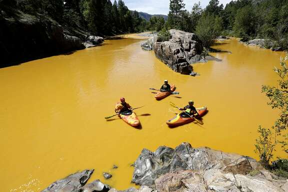FILE - In this Aug. 6, 2015, file photo, people kayak in the Animas River near Durango, Colo., in water colored from a mine waste spill. U.S. prosecutors have declined to pursue criminal charges against an employee of the Environmental Protection Agency over a massive mine wastewater spill that fouled rivers in three states, a federal watchdog agency said. The EPA's Office of Inspector General disclosed Wednesday, Oct. 12, 2016, that it recently presented evidence to prosecutors that the unnamed employee may have violated the Clean Water Act and given false statements. (Jerry McBride/The Durango Herald via AP, File)