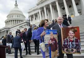 US Senator Patrick Leahy (R), Democrat of Vermont, and US Senator Dianne Feinstein (2nd R), Democrat of California, stand alongside Democratic Senators as they hold photos of people who would lose their health coverage under the Senate Republicans' healthcare bill during a press conference at the US Capitol in Washington, DC, June 27, 2017. / AFP PHOTO / SAUL LOEBSAUL LOEB/AFP/Getty Images