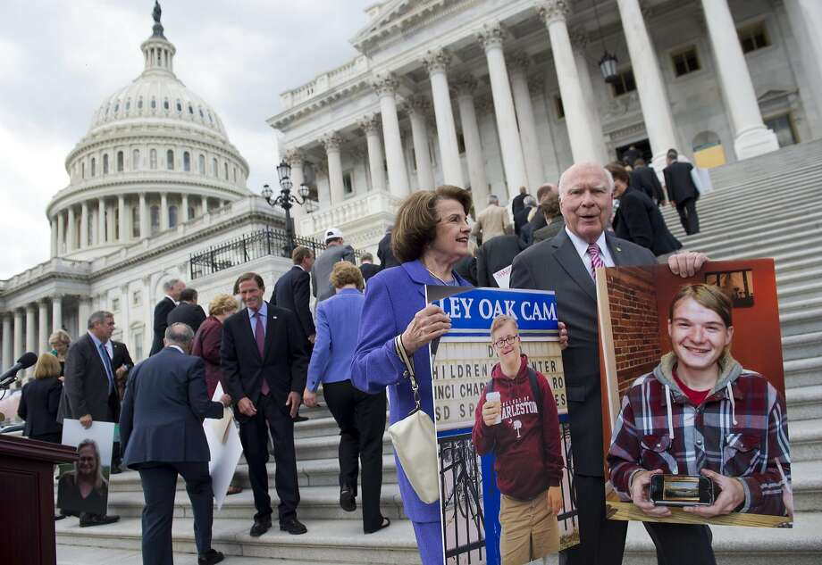 Sen. Dianne Feinstein (front left) and Vermont Sen. Patrick Leahy stand with other Democratic senators as they hold photos of people who would lose health care coverage under the GOP bill. Photo: SAUL LOEB, AFP/Getty Images