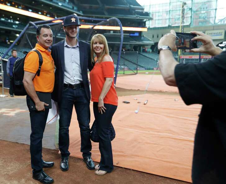 Joe Perez, 17, the Astros second-round pick, gets his photo taken with his parents after signing with the team during batting practice before an MLB baseball game at Minute Maid Park, Tuesday, June, 27, 2017.