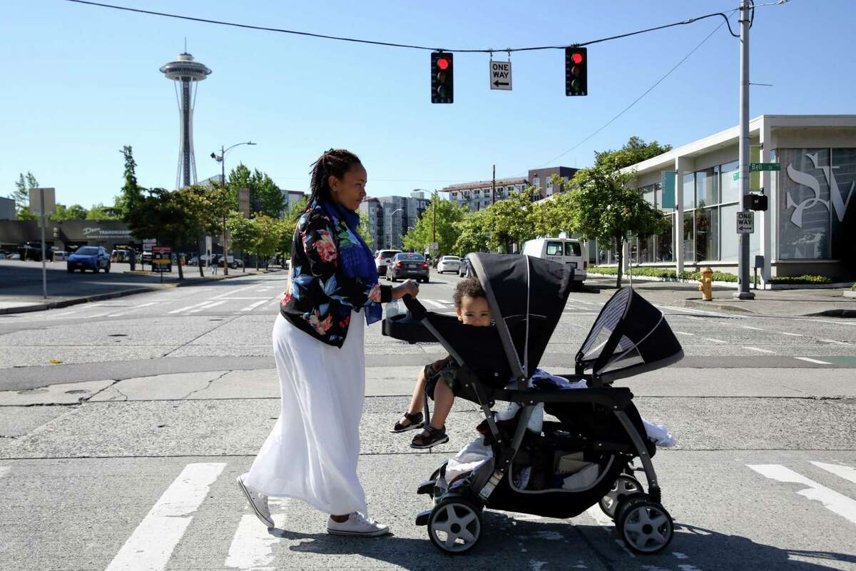 Madina Jafari pushes a stroller with her two young sons in it down Bell Street from the Mary's Place day center to the shelter where they have been living for the past few months.