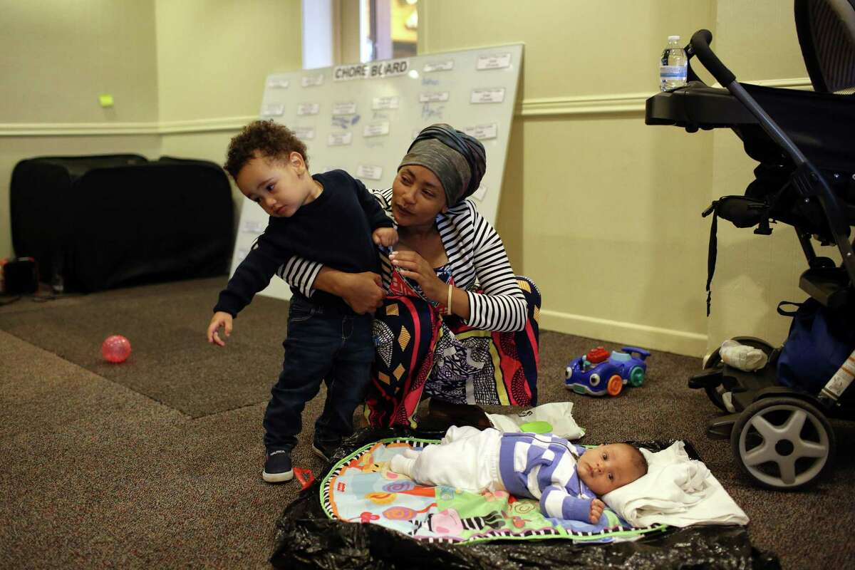 Madina Jafari, a refugee from Ethiopia, plays with her sons Alraman, 2, and Arsam, 1 month, in the day center available for Mary's Place residents to be during the hours between 8 am and 4:30 pm when the shelter is closed. Before finding Mary's Place, Medina and her family lived on the streets of SeaTac while she was nine months pregnant.