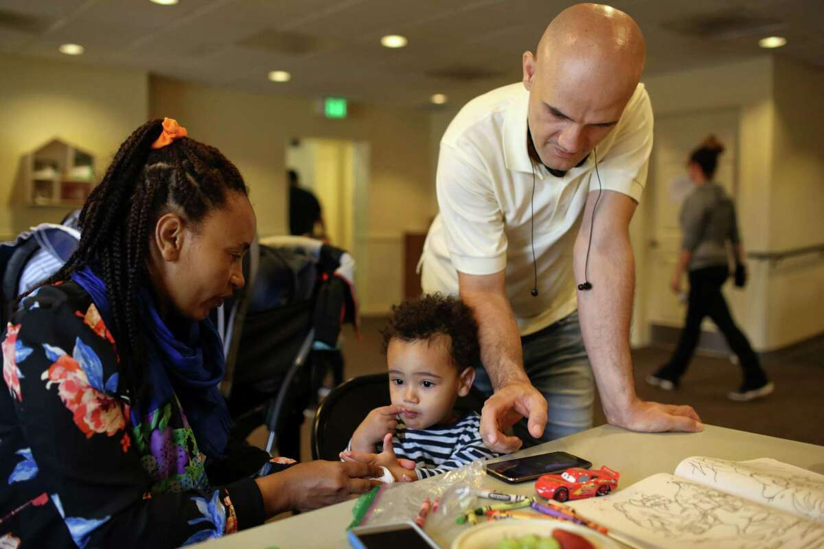 Ebrahim, right, and Madina Jafari look after their son Alraman, 2, in the Mary's Place day center, June 26, 2017. The couple met and married at a refugee camp in Kenya, before moving to Seattle two months ago, by way of Buffalo, New York.