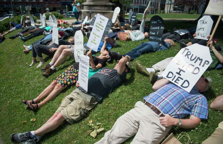 """Local concerned citizens gather to protest the current health care bill being considered in the Senate with a """"Die-in"""" at the Monroe County Courthouse in Bloomington, Ind. Monday, June 26, 2017. (Chris Howell/The Herald-Times via AP) Photo: Chris Howell, MBI / The Herald-Times, 2017"""
