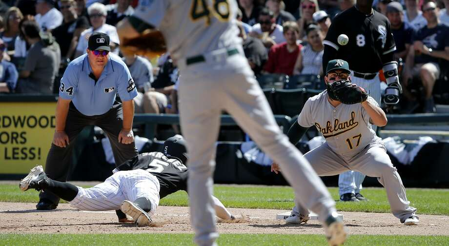 Chicago White Sox's Yolmer Sanchez (5) dives safely back to first as Oakland Athletics starting pitcher Daniel Gossett throws a pickoff-attempt to first baseman Yonder Alonso (17) as first base umpire Sam Holbrook, left, watches during the fifth inning of a baseball game Saturday, June 24, 2017, in Chicago. (AP Photo/Charles Rex Arbogast) Photo: Charles Rex Arbogast, Associated Press