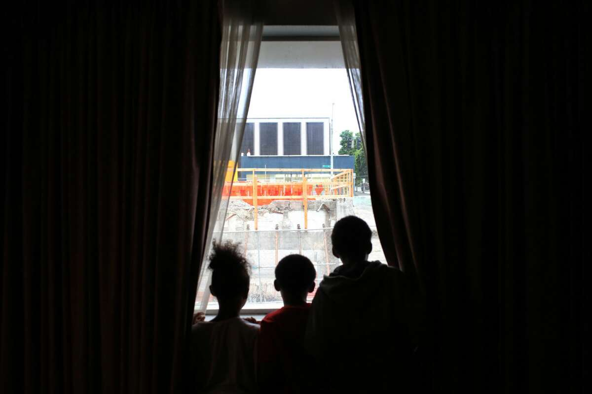 Dee's daughter, 7, and two sons, 9 and 11, look out the window of their room in the Mary's Place shelter at the construction of a new Amazon building in the lot next door. (Genna Martin, seattlepi.com)