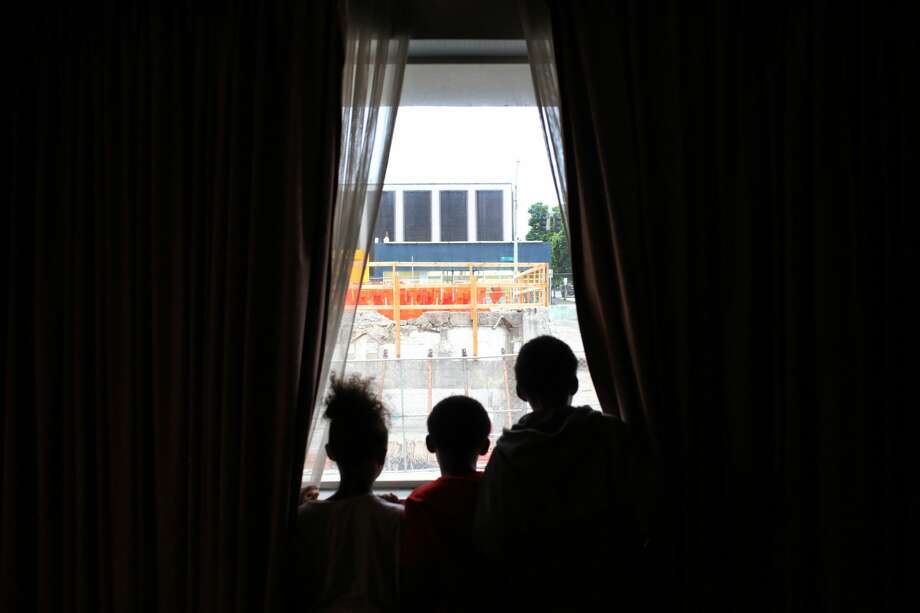 Dee's daughter, 7, and two sons, 9 and 11, look out the window of their room in the Mary's Place shelter at the construction of a new Amazon building in the lot next door. (Genna Martin, seattlepi.com) Photo: GENNA MARTIN, SEATTLEPI.COM